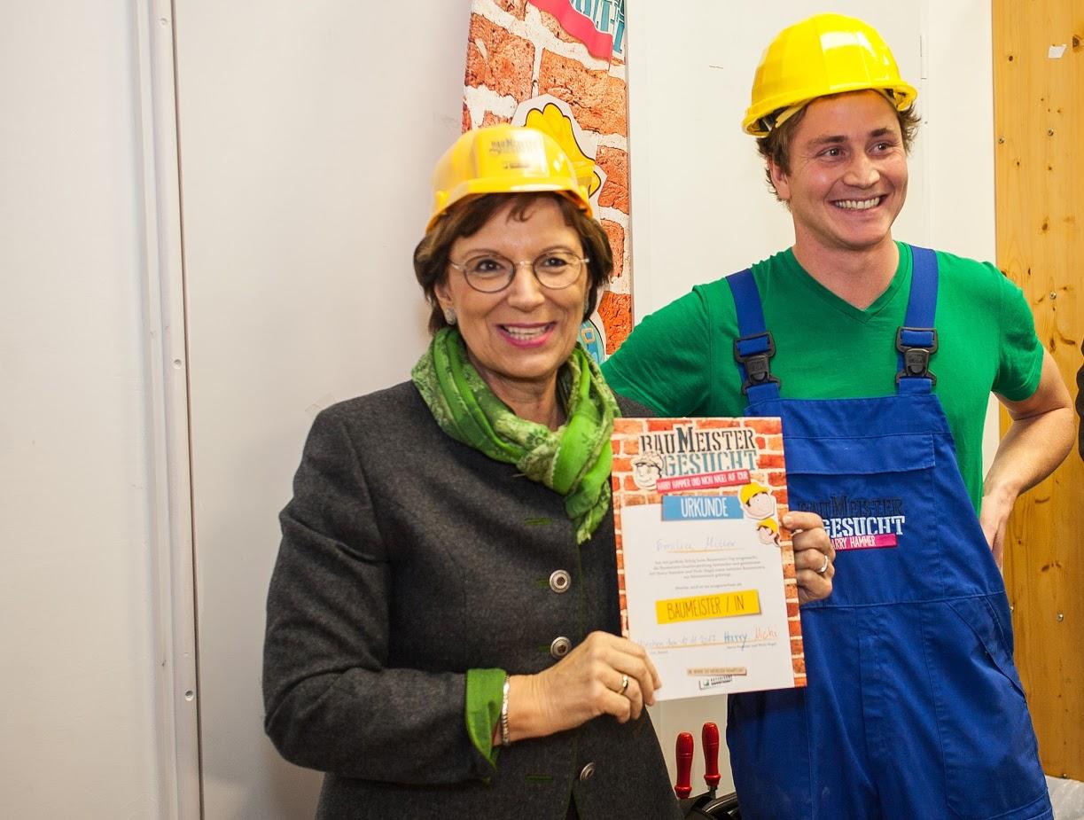 Nagelprobe bestanden: Bayerns Familienministerin Emilia Müller präsentiert stolz ihr Baumeister-Diplom, dass von Harry Hammer unterschrieben wurde. © MPA/C.Oliver