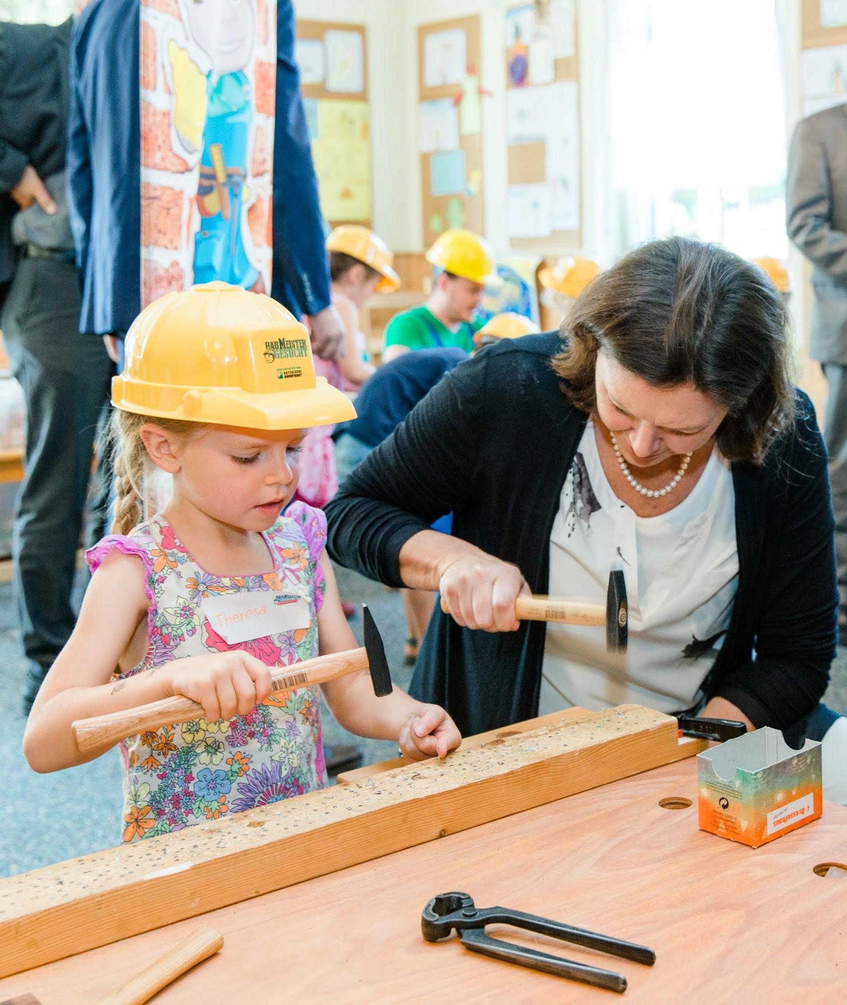 Bauministerin Ilse Aigner mit Nachwuchs-Baumeisterin bei der 'Nagelprobe' (c) Schwaiger/bbiv